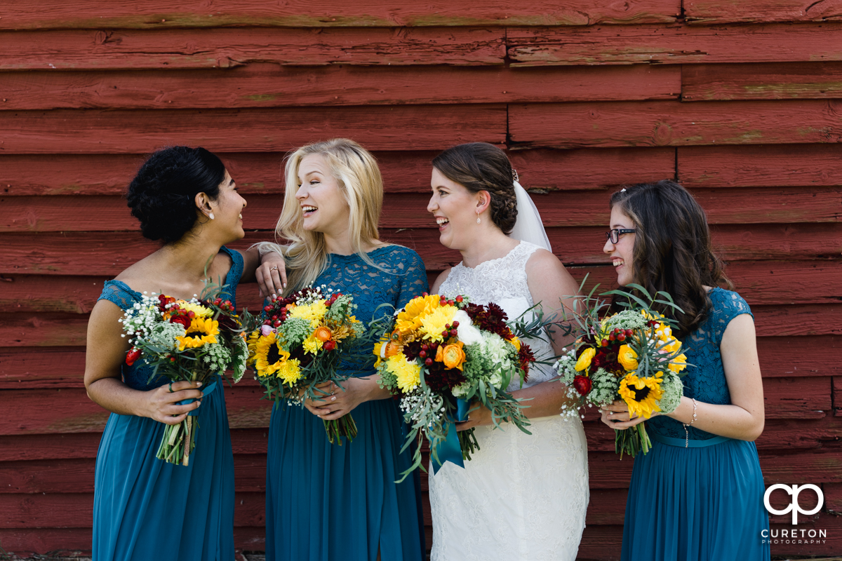 Bride laughing with bridesmaids in front of a red barn.