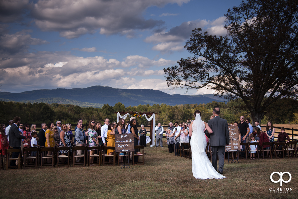 Bride and her father walking down the aisle at Famoda Farms with the mountains in the background.