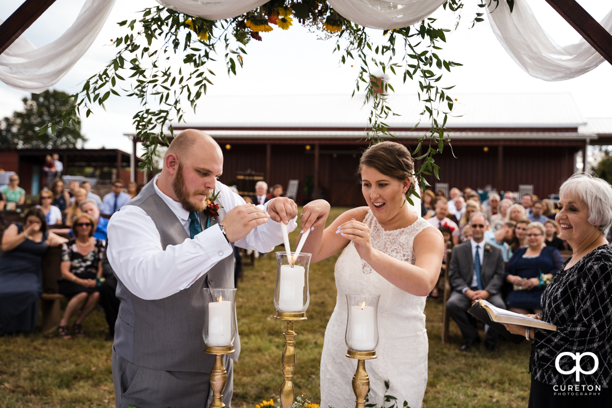 Groom and bride lighting a unity candle.