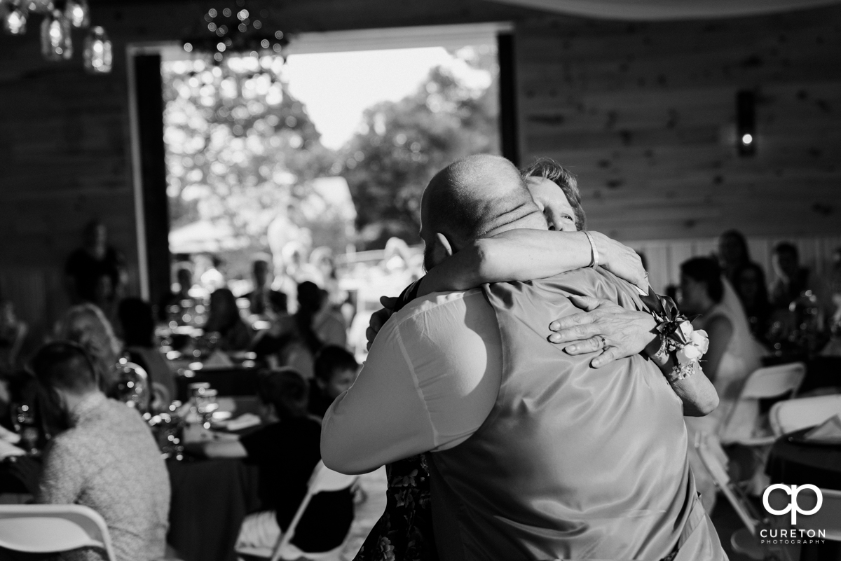 Groom hugging his mom at the wedding reception.