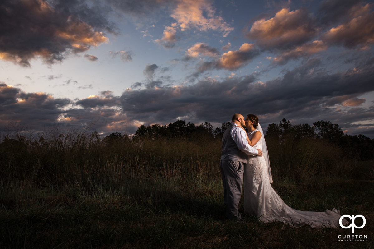 Groom kissing his bride in a field at Famoda Farms after the wedding reception.