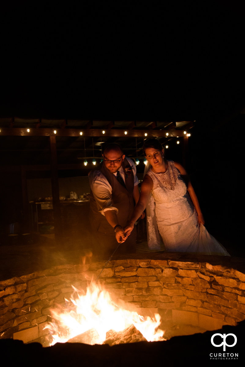 Bride and groom toasting a marshmallow by the fire.