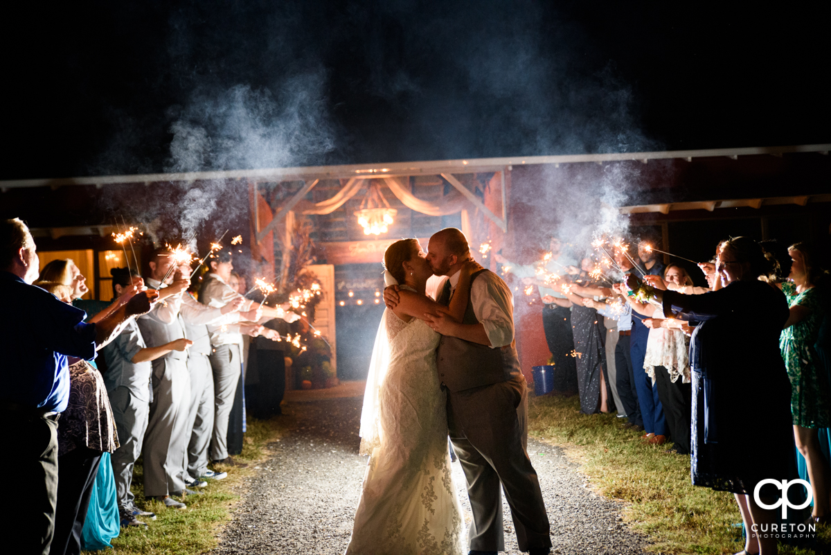 Bride and groom making an epic grand exit though sparklers.