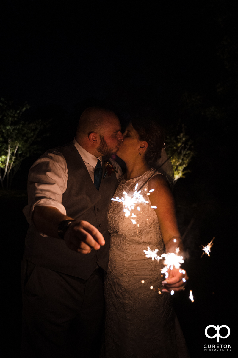 Bride and groom kissing while holding sparklers.