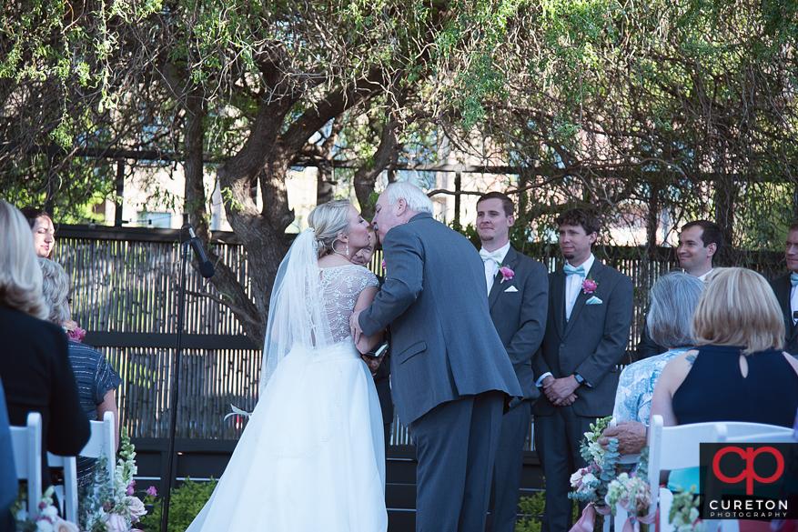 Father kisses the bride.