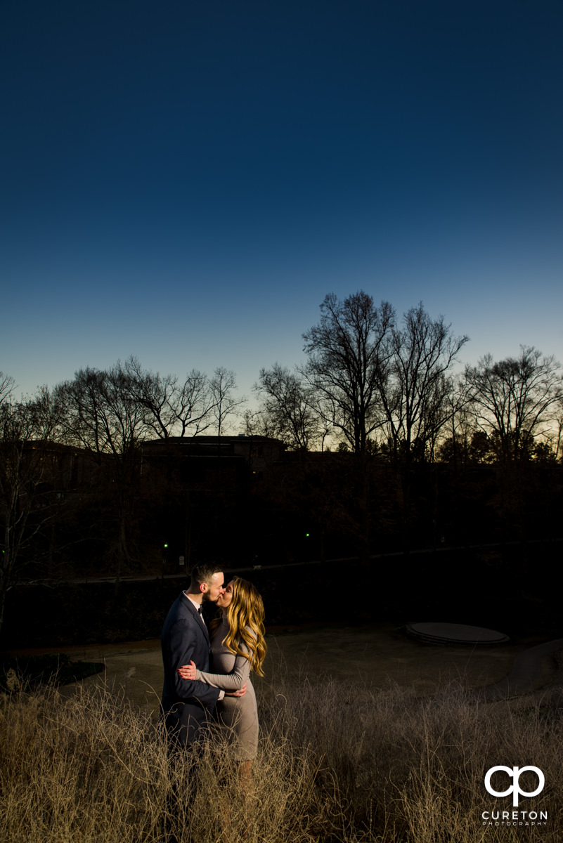 Future bride and groom standing in some tall grass during a Falls Park engagement session in downtown Greenville,SC.