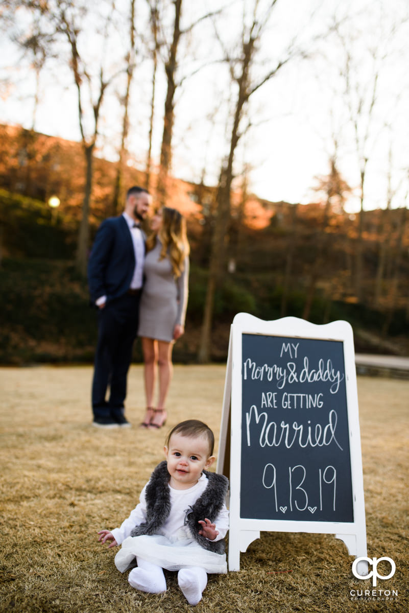 Engaged couple in the background as their baby daughter sits near a sign about their wedding for a save the date photo.