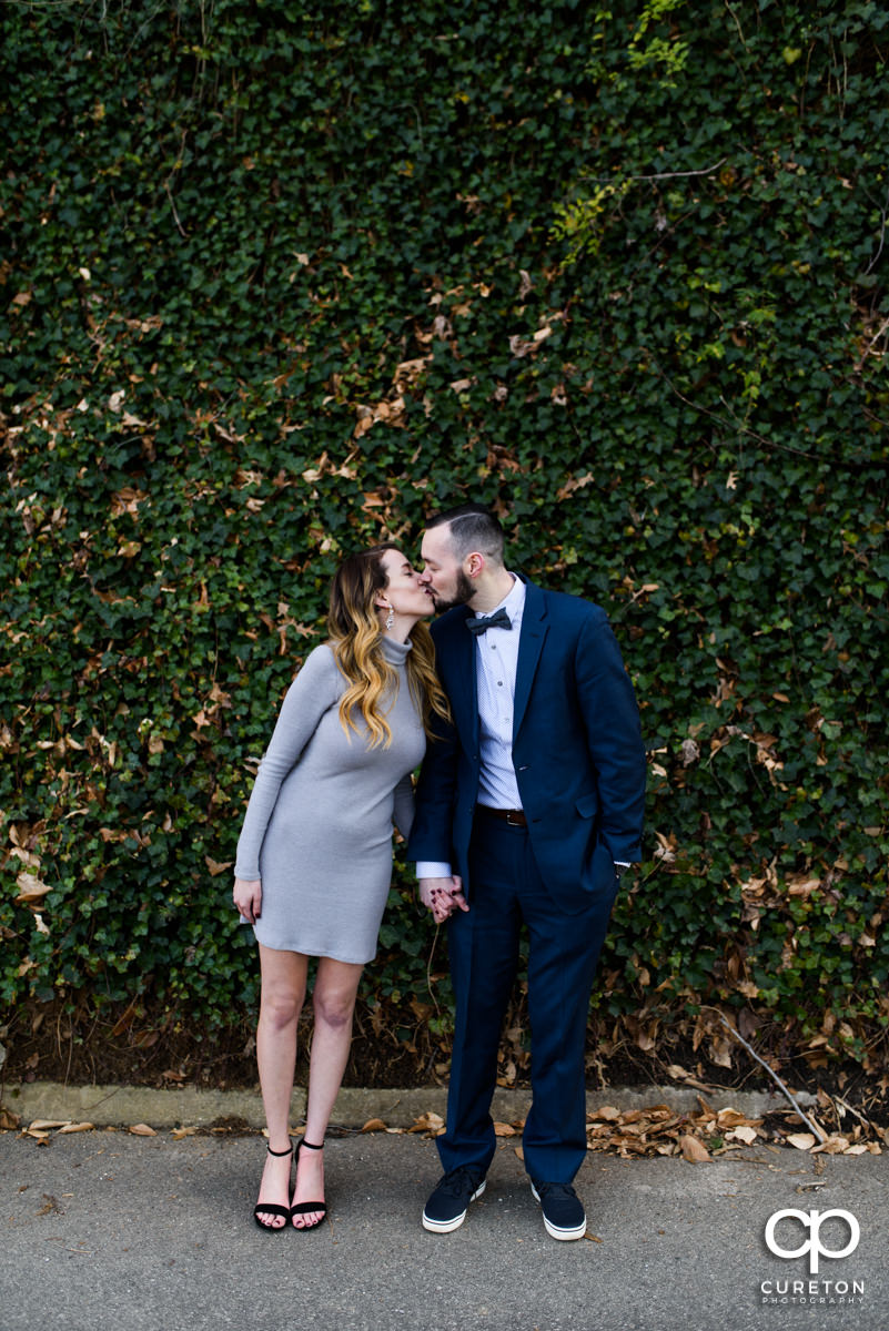 Man kissing his fiancee in front of a wall of ivy in Falls Park in Greenville.