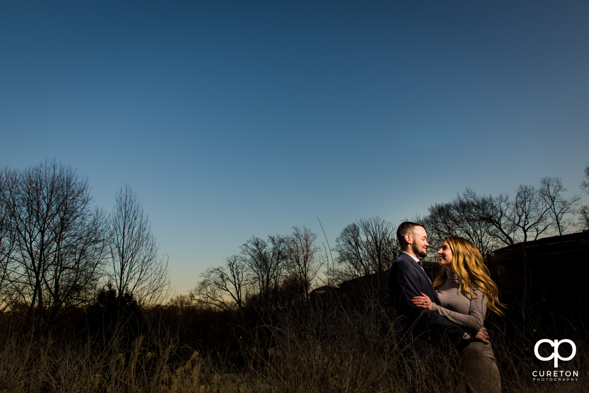 Man holding his fiancee at sunset during an engagement session.