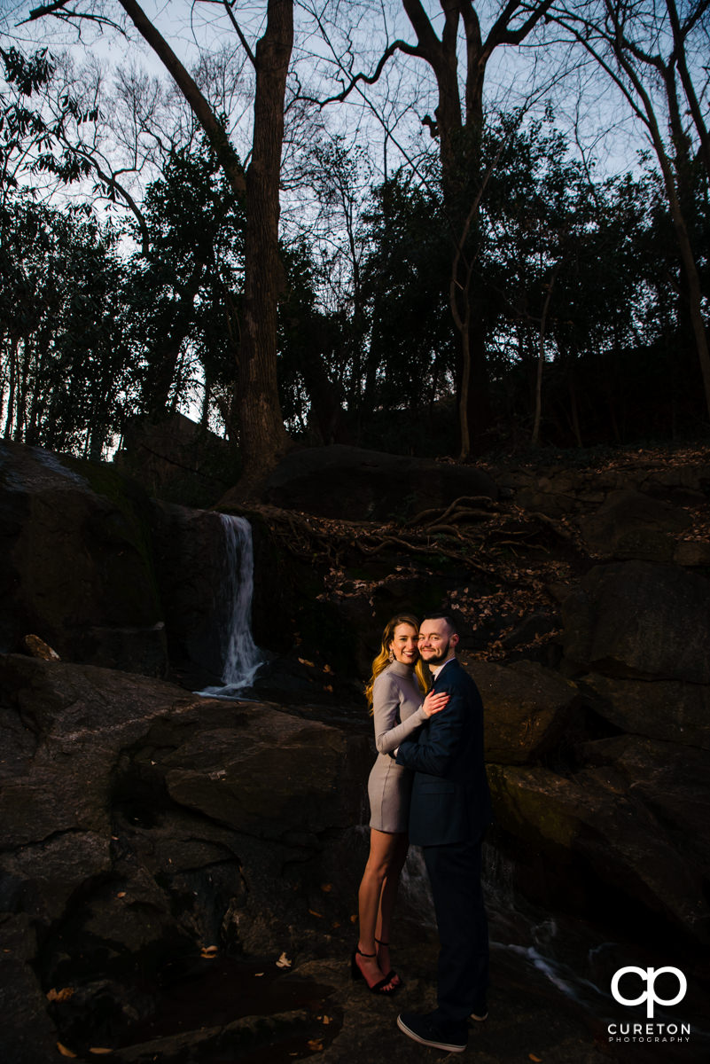 Engaged couple standing in front of a waterfall.
