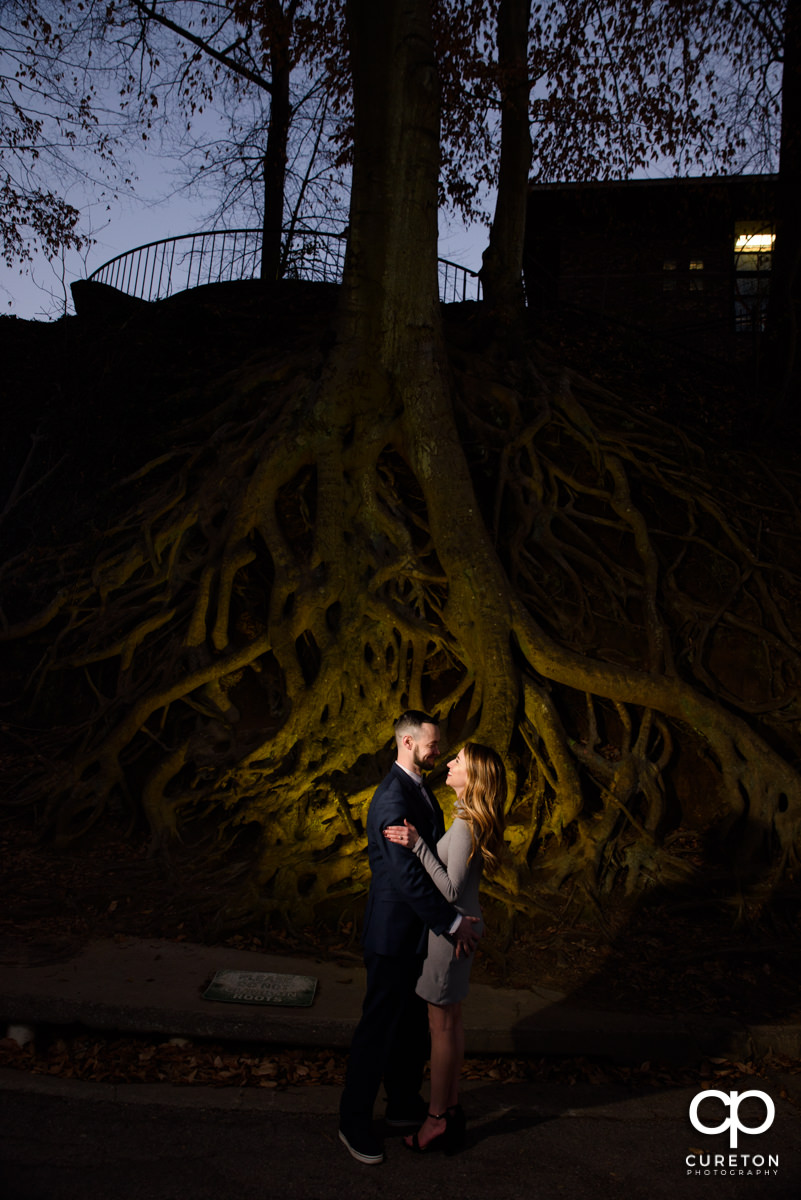 Future bride and groom standing in front of the landmark tree roots in Falls Park during an engagement session in downtown Greenville,SC.