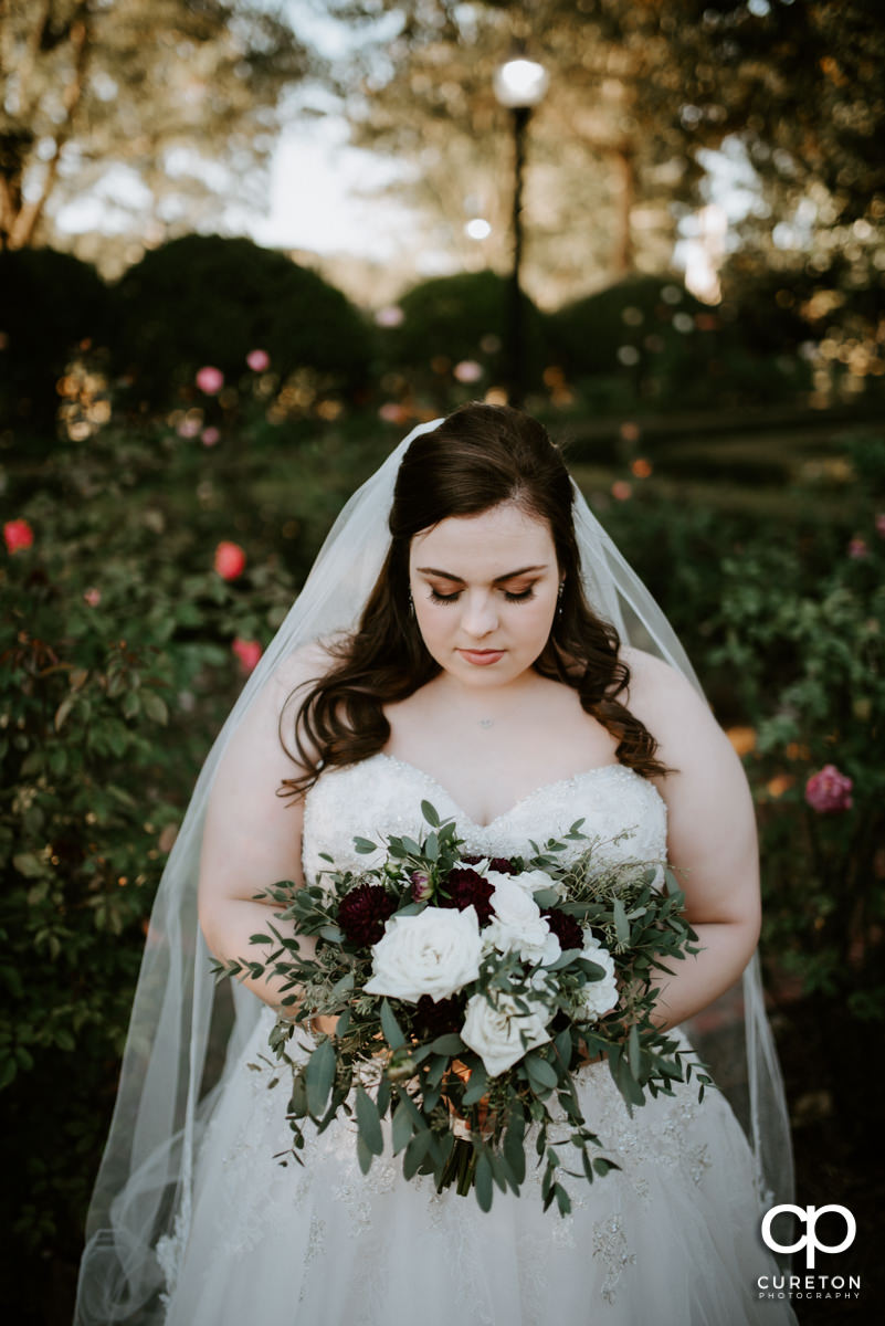 Bride holding her bouquet in the rose garden at Furman University.