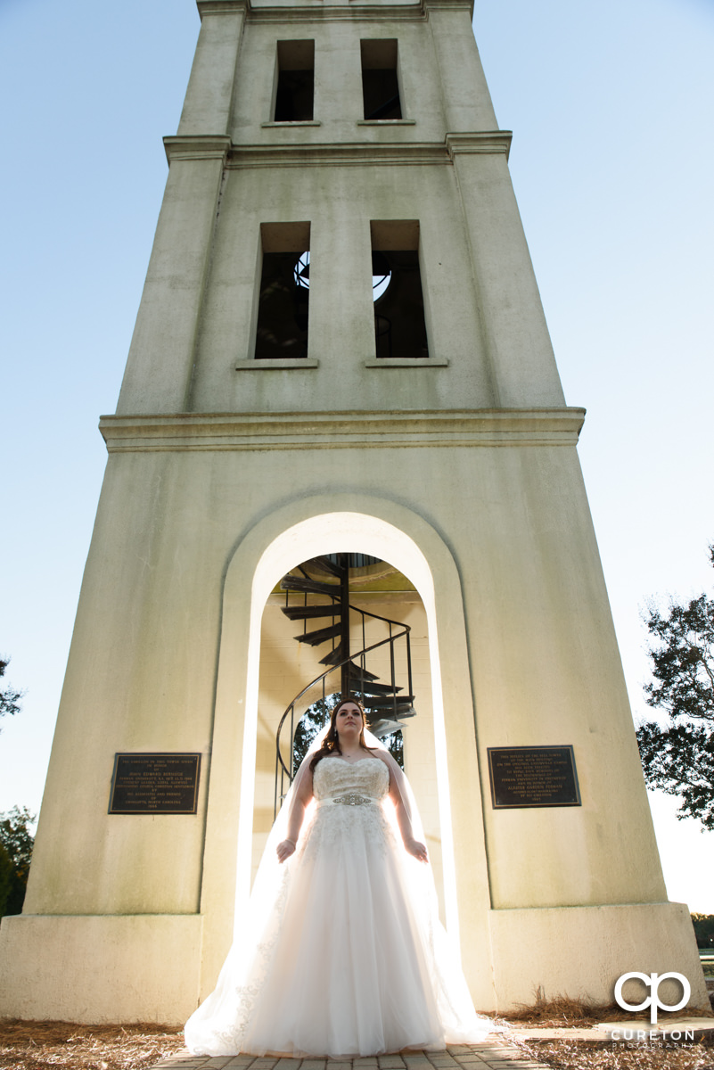 Bride holding her veil by the bell tower at Furman University.