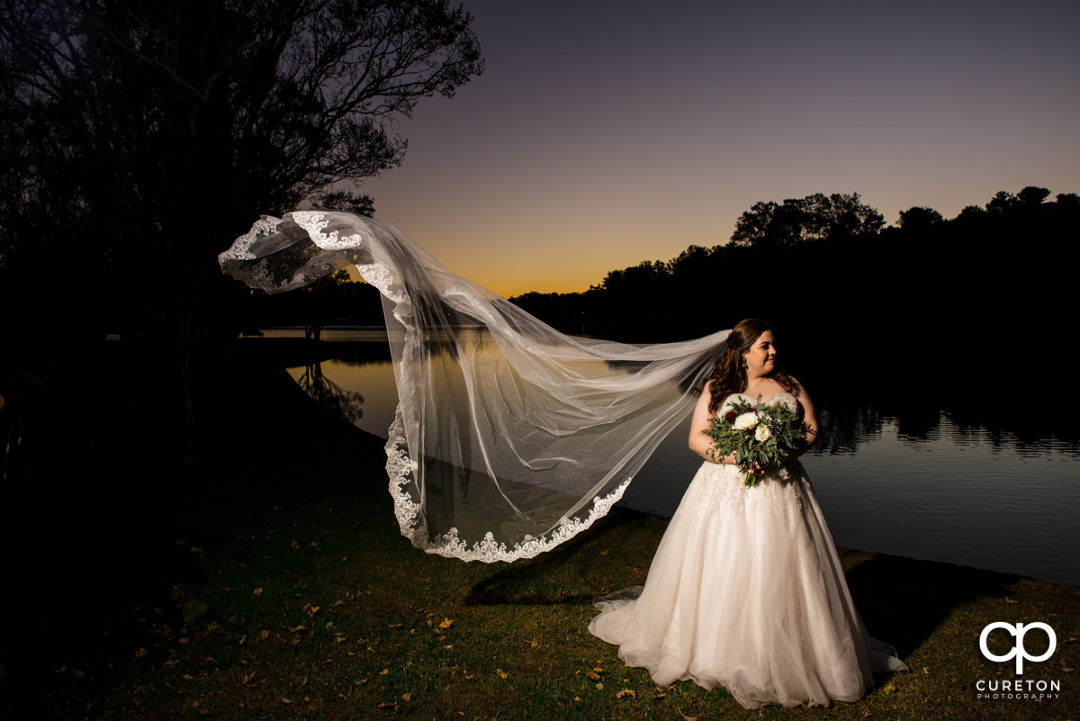 Bride with her veil blowing in the wind by a lake at sunset at Furman University during her bridal session.