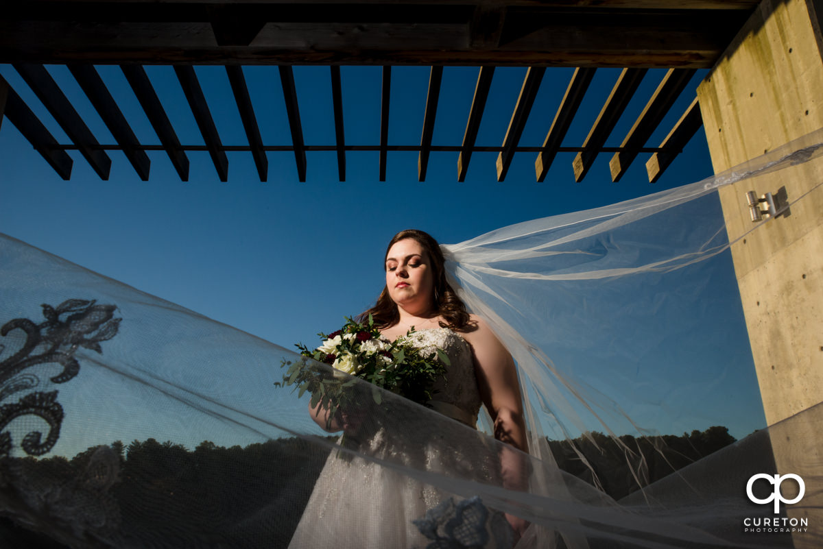 Bride with her veil blowing in the wind in front of a vibrant blue sky at Furman University.