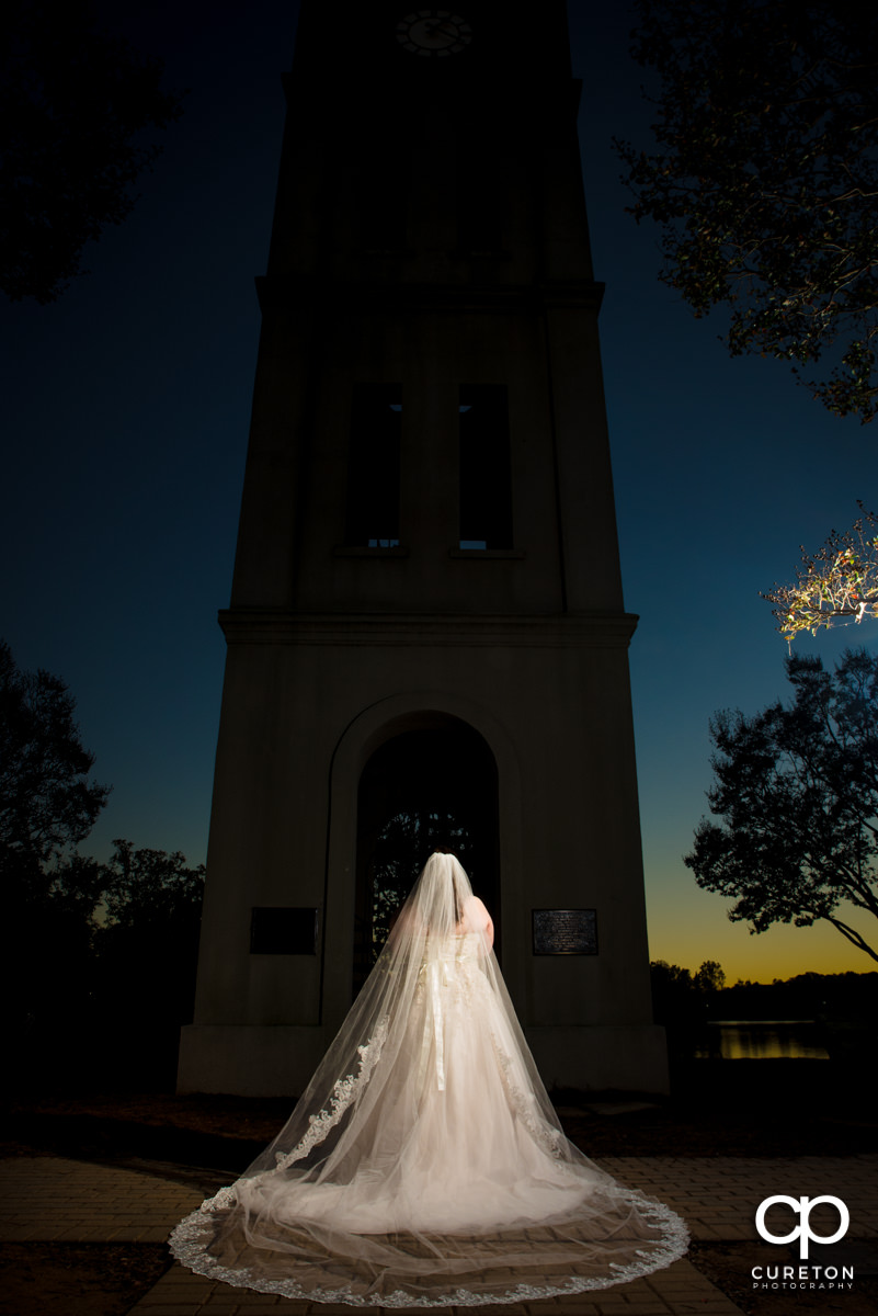 Bride showing the back of her dress and long veil at sunset during a Furman University Bridal.