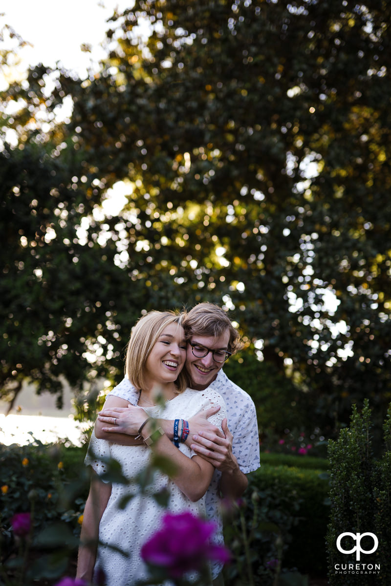 Man hugging his fiancee from behind in the rose garden during their college graduation and engagement session at Furman University.