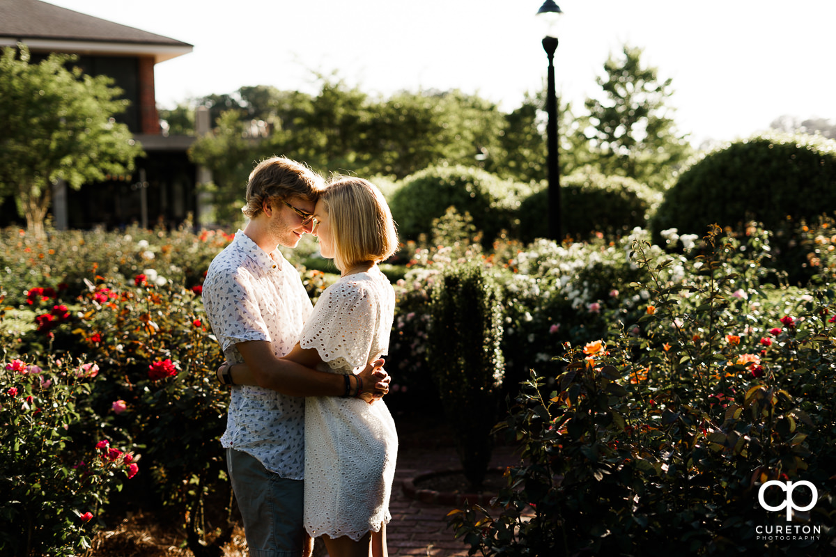 Engaged couple dancing in the garden during their college graduation and engagement session at Furman University.