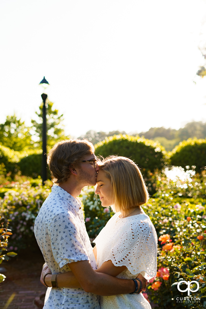 Man kissing his fiancee on the forehead during their college graduation and engagement session at Furman University.