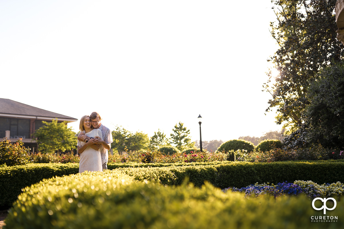 Engaged couple sharing a moment in the rose garden during their college graduation and engagement session at Furman University.