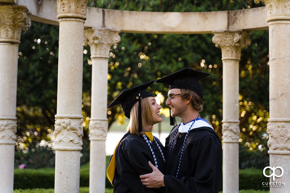 Two Furman Graduates in their cap and gowns during their college graduation and engagement session at Furman University.