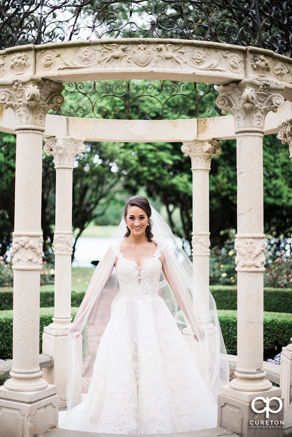 Bride holding her long veil during her Furman rose garden bridal session.