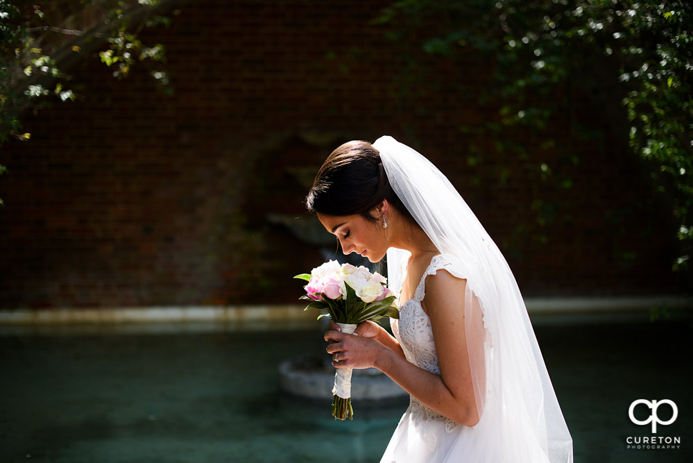 Bride smelling her flowers during her Furman rose garden bridal session in Greenville,SC.
