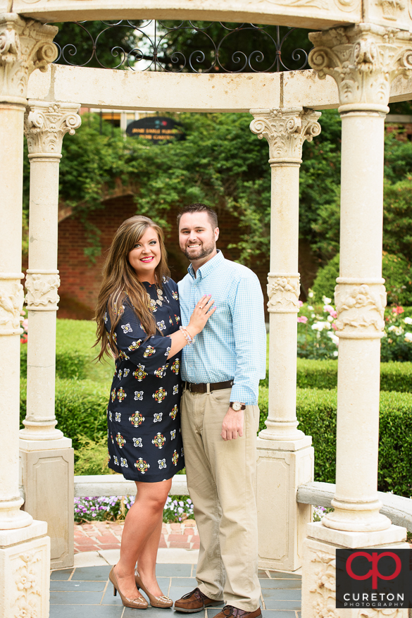 Engaged couple in a rose garden arbor.