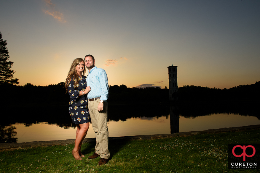 Couple by the lake at sunset at Furman with the Bell tower in the background.