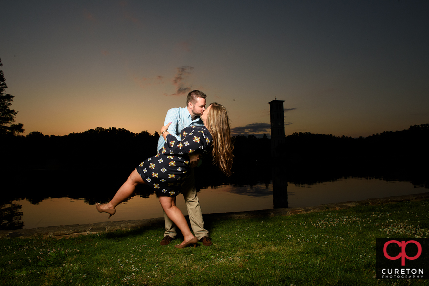 Enaged couple dancing by a lake at sunset.