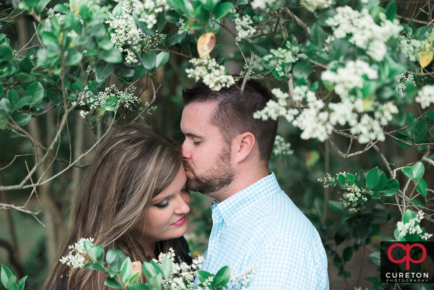Engaged couple surrounded by blooming flowers.