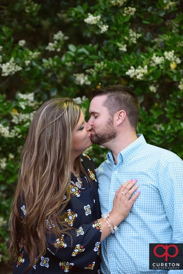 Engaged couple kissing.