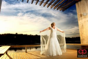A bride with a long veil by the lake at sunset during her Furman University bridal session.