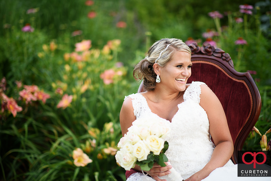 A bride in a victorian chair in flowers.