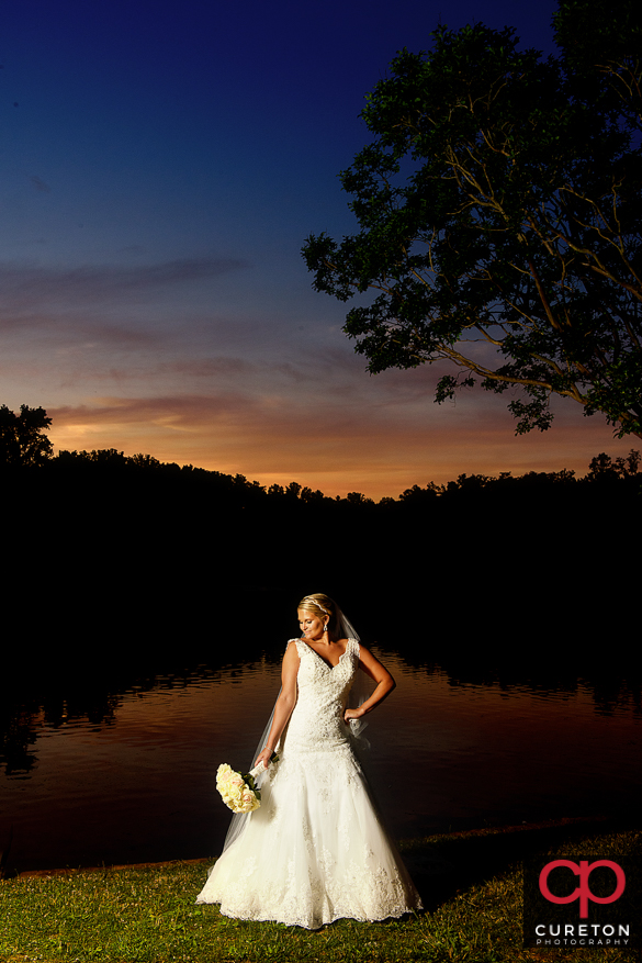 A bride posing by the lake at sunset during her Furman University bridal session..