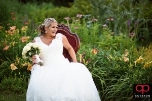 Bride posing in a red vintage chair in some flowers during her Furman University bridal session.