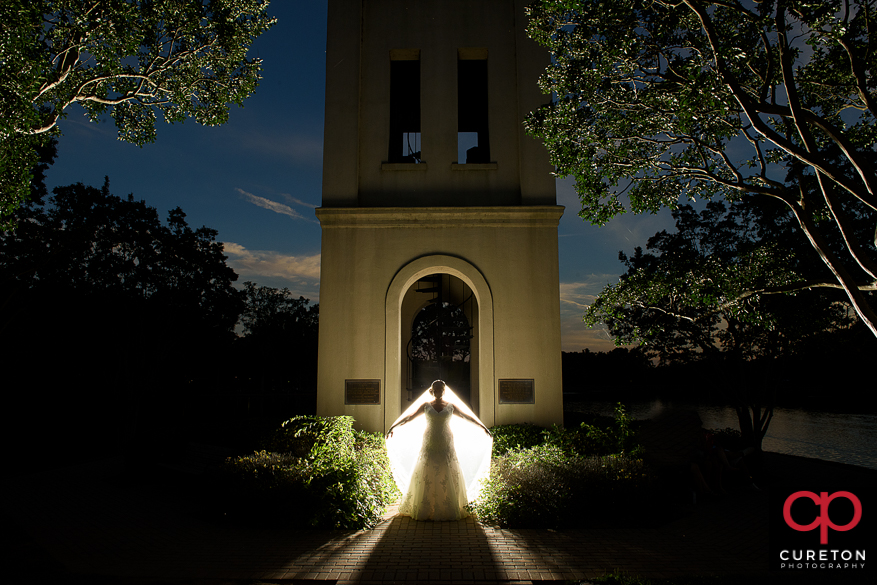 Backlit shot of a bride at the Bell Tower at Furman University by the lake.