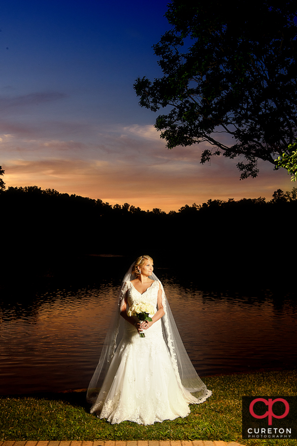 Bride by the lake at Furman during an epic sunset at her bridal session.