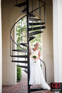 Bride standing on a staircase outside.