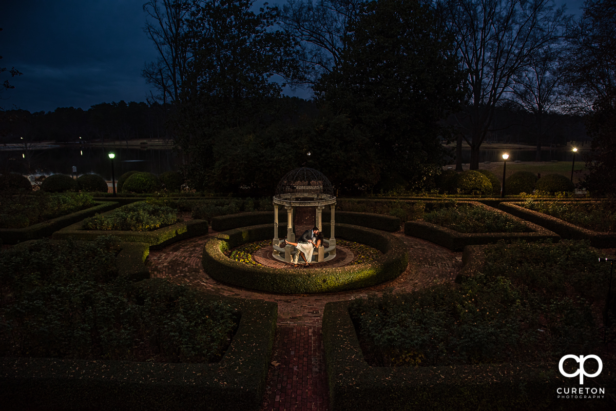 Future bride and groom dancing in the rose garden at night during their Furman University engagement session.