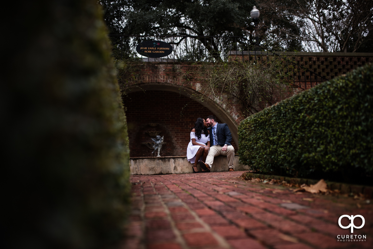 Bride and groom kissing in the rose garden during their Furman University engagement session.