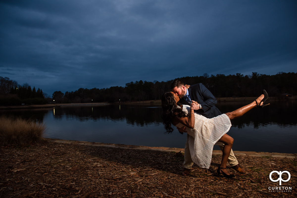 Engaged couple dancing by the lake during a Furman University engagement session.