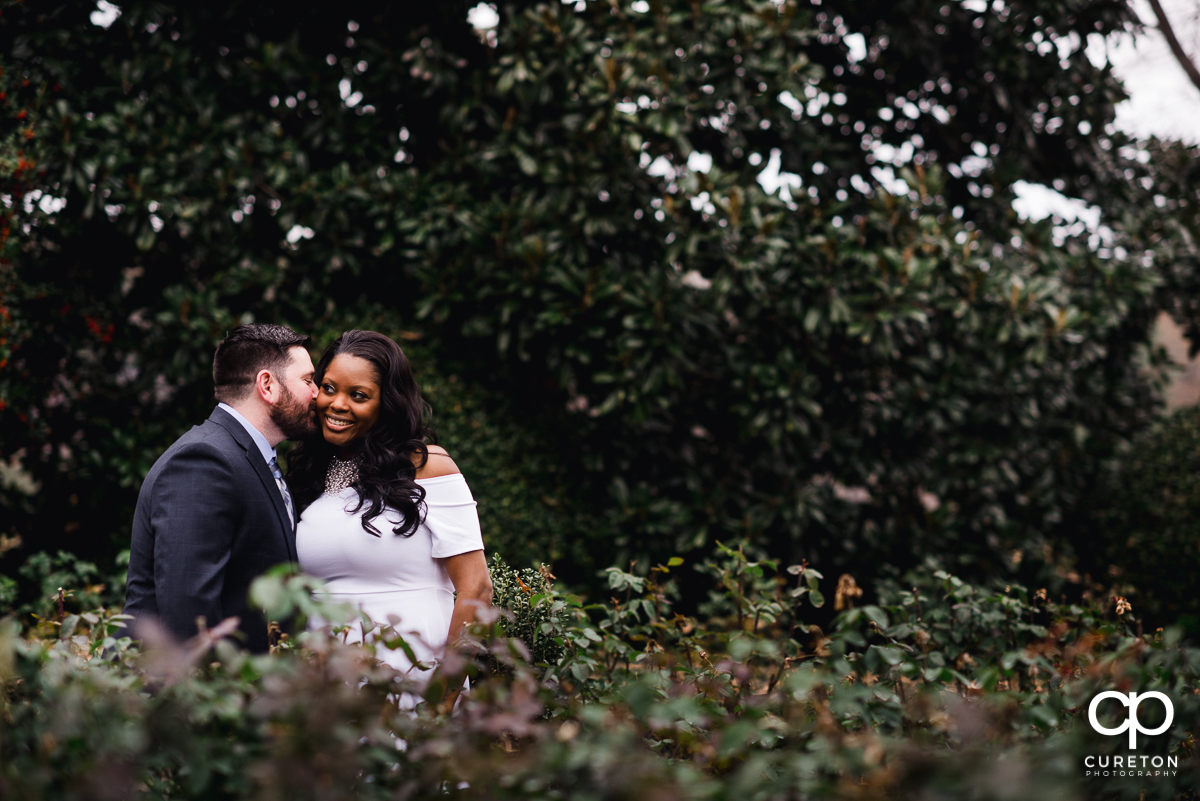 Groom whispering in his bride's ear as they stroll in the rose garden at Furman University.