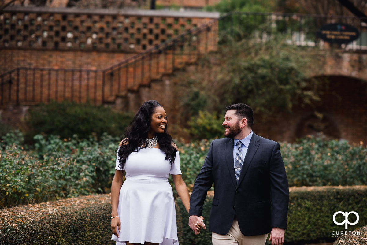Engaged couple walking in the rose garden at Furman.