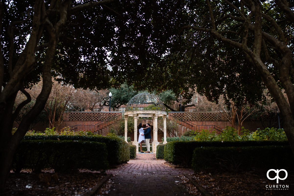 Engaged couple standing in the middle of the gazebo in the rose garden during their Furman University engagement session.