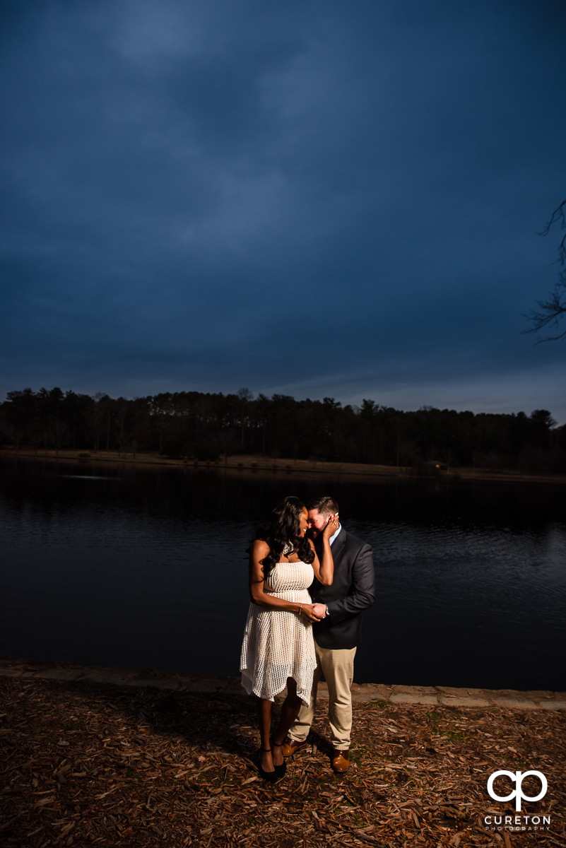 Engaged couple hugging beside the Furman lake at sunset.