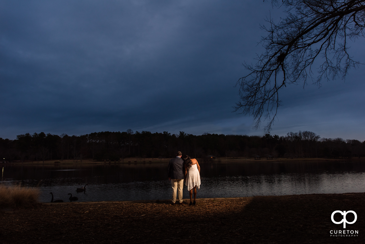 Bride and groom looking out into sunset by the lake at Furman University.