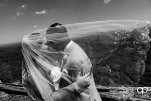 Bride and groom snuggling at Glassy Chapel with her veil blowing in the wind over their faces after their wedding.