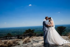 Bride and groom standing on top of a rock at the Cliffs at Glassy Chapel.