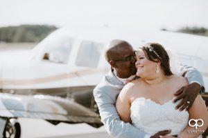 Groom hugging his bride beside an airplane.